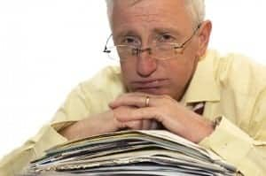 older man leaning pile paper looking overwhelmed 640 x 425