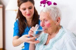 Alzheimer's woman who needs assistance to drink out of a glass needs Alzheimer's & Dementia planning